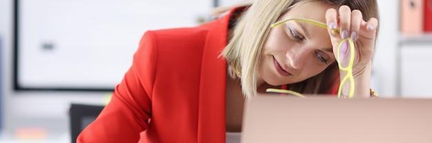 Zmęczona kobieta siedzi przy laptopie z okularami w dłoniach