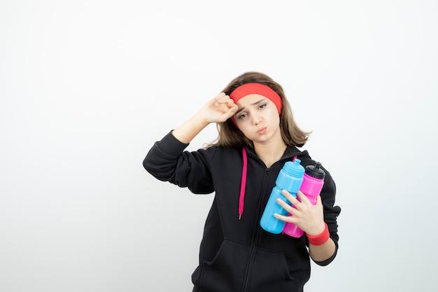 Zmęczona kobieta sportowy trzymając butelki z wodą na białej ścianie.