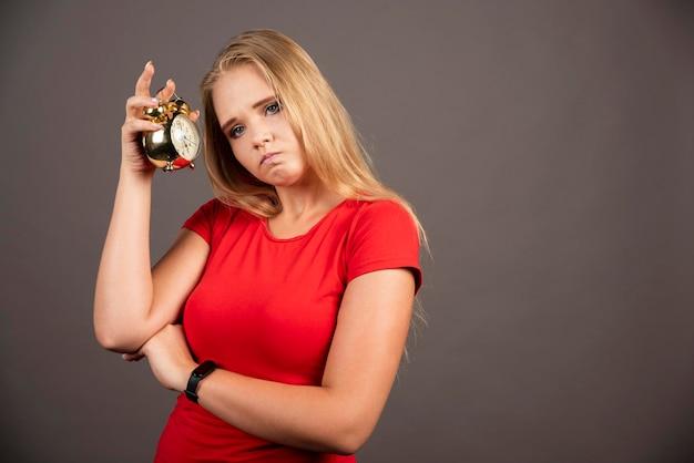 Zmęczona kobieta stojąca z zegarem na ciemnym tle. wysokiej jakości zdjęcie