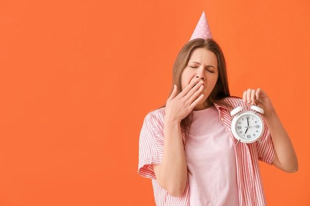 Zmęczona kobieta świętująca urodziny z budzikiem na tle koloru