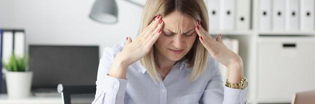Zmęczona kobieta trzyma palce na skroniach przy stole roboczym koncepcja nieregularnego dnia pracy