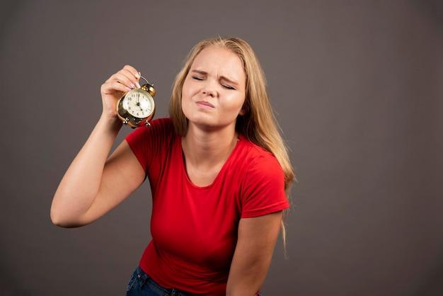 Zmęczona kobieta trzyma zegar na ciemnym tle. wysokiej jakości zdjęcie