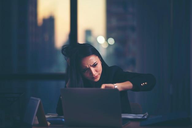 Zmęczona kobieta w domowym biurze patrzeje jej zegarek