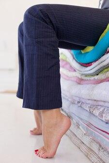 Zmęczona kobieta w spodniach siedząca bosymi stopami na stosie materacy odpoczywająca po dniu pracy