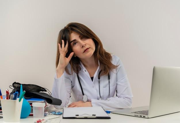 Zmęczona kobieta w średnim wieku ubrana w szlafrok medyczny ze stetoskopem siedząca przy biurku praca na laptopie z narzędziami medycznymi kładąca dłoń na głowie na białym tle z miejsca na kopię
