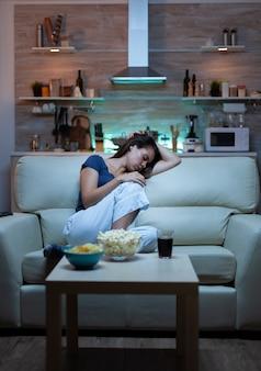 Zmęczona kobieta zamykająca oczy podczas oglądania filmu w nocy. zmęczona, wyczerpana, samotna, śpiąca gospodyni domowa w piżamie śpi przed telewizorem, siedząc na wygodnej kanapie w salonie w domu.