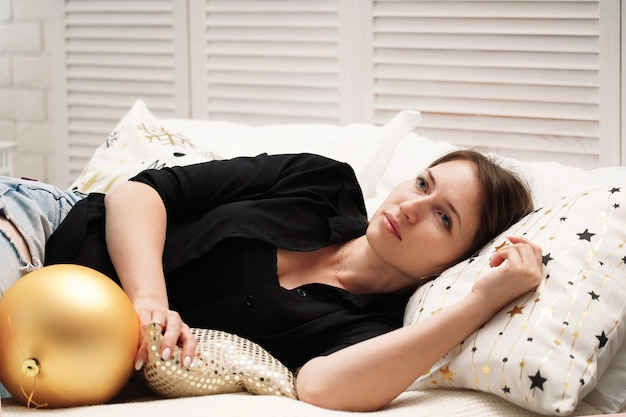 Zmęczona kobieta zasypia, leżąc na łóżku. wyczerpany i upadł bez sił. rzucił sam w nowym roku. samotność w łóżku, nikt nie jest obecny. zmęczony świętami bożego narodzenia. same wakacje bez rodziny