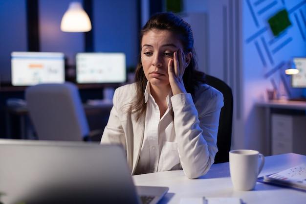 Zmęczona kobieta zasypia, sprawdzając analizę finansową późno w nocy w biurze firmy rozpoczynającej działalność