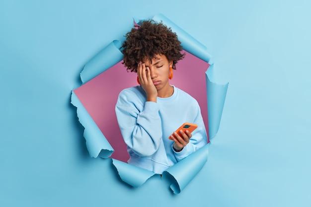 Zmęczona kobieta znużona surfowaniem po internecie sprawia, że twarz dłoni za pomocą nowoczesnego smartfona zamyka oczy nosi swobodny sweter przebijający się przez papierową ścianę
