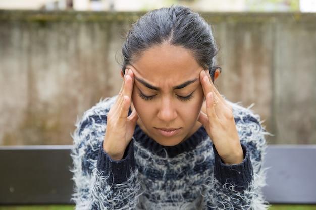 Zmęczona ładna młoda kobieta dotyka świątynie outdoors