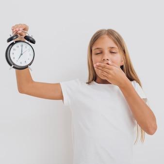 Zmęczona mała dziewczynka trzyma zegar up