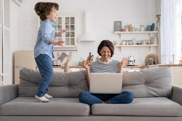 Zmęczona matka siedzi na kanapie, pracuje na laptopie w domu, nadpobudliwe małe dziecko podskakuje, zwracając uwagę.