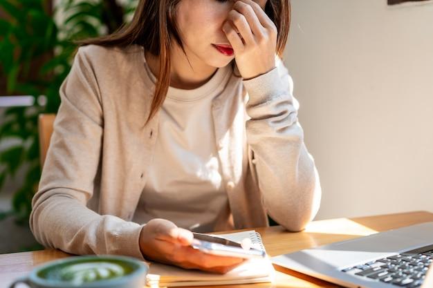 Zmęczona młoda azjatka siedząca w kawiarni, pracująca z laptopem i filiżanką kawy