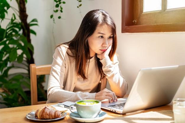 Zmęczona młoda azjatka siedząca w kawiarni przy filiżance kawy i rogaliku
