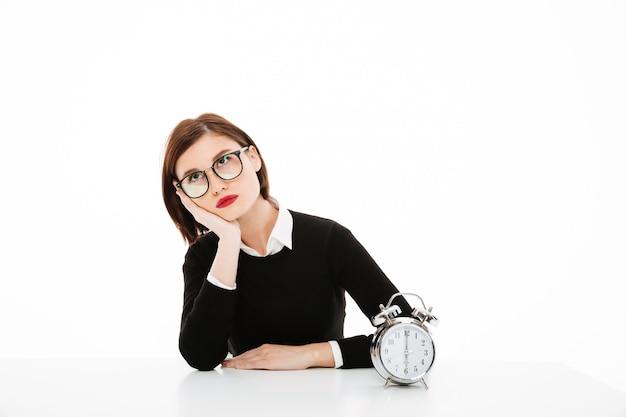Zmęczona młoda biznesowa dama jest ubranym szkła