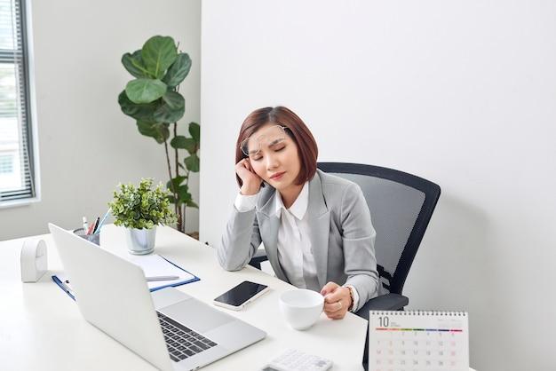 Zmęczona młoda bizneswoman relaksująca się przy biurku z zamkniętymi oczami i głową opartą na dłoni