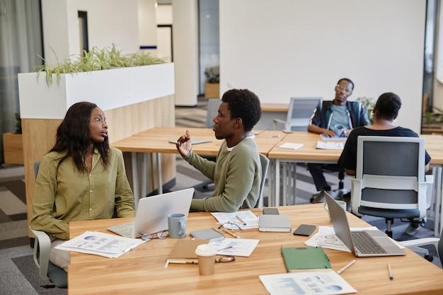 Zmęczona młoda bizneswoman słucha współpracownika, który próbuje udowodnić swój punkt widzenia w rozmowie o nowym ...