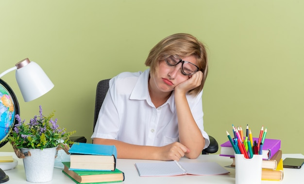 Zmęczona młoda blond studentka w okularach siedząca przy biurku ze szkolnymi narzędziami trzymająca rękę na twarzy z zamkniętymi oczami