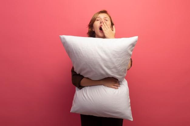 Zmęczona młoda blondynka przytula poduszkę ziewając trzymając rękę przy ustach z zamkniętymi oczami