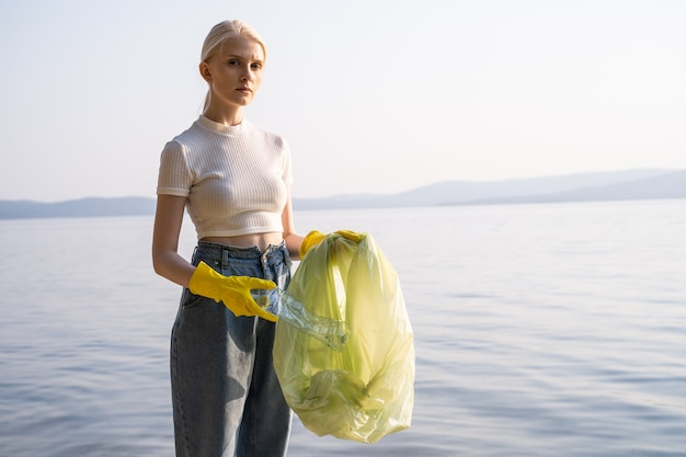 Zmęczona młoda blondynka w gumowych rękawiczkach z workiem na śmieci na jeziorze. oczyszczanie środowiska i zbiorników.