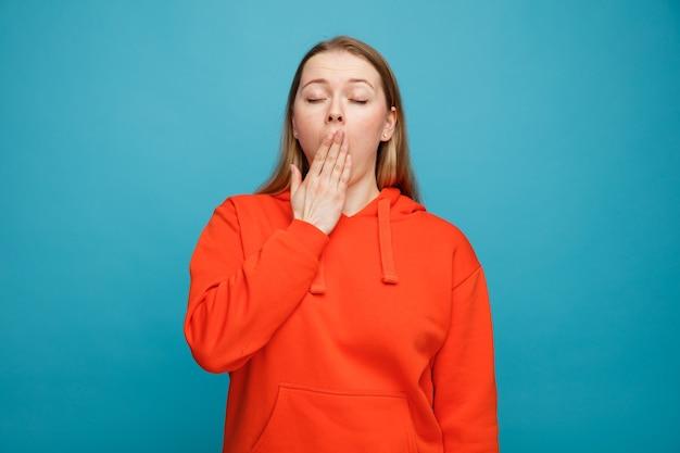 Zmęczona młoda blondynka ziewanie, trzymając rękę na ustach z zamkniętymi oczami