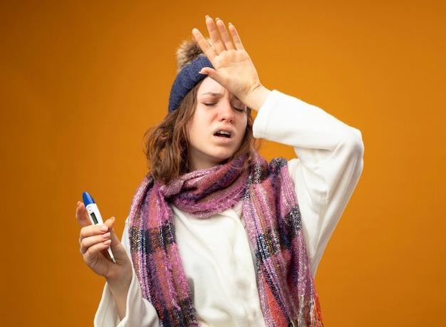 Zmęczona młoda chora dziewczyna ubrana w białą szatę i czapkę zimową z szalikiem trzymając termometr kładąc rękę na czole na białym tle na pomarańczowej ścianie