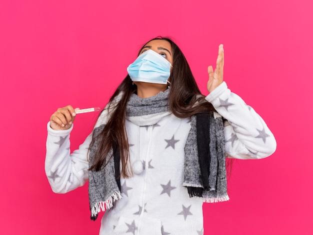 Zmęczona młoda chora dziewczyna ubrana w maskę medyczną z szalikiem trzymając termometr, podnosząc rękę na różowym tle