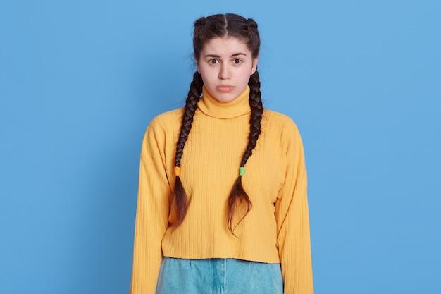 Zmęczona młoda ciemnowłosa kobieta zaciska usta, czuje smutek, ubrana w żółty sweter, odizolowana na niebieskiej ścianie
