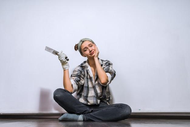 Zmęczona młoda dziewczyna w kraciastej koszuli siedzi na podłodze i trzyma szpatułkę