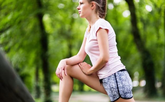 Zmęczona młoda joggerka odpoczywająca po joggingu