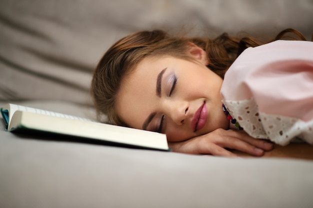 Zmęczona młoda kobieta drzemie w domu, leżąc na kanapie z książką