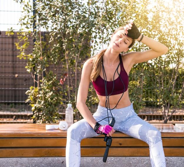 Zmęczona młoda kobieta fitness wycieranie jej potu, trzymając skakanka wokół szyi