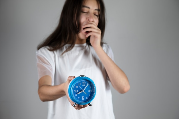 Zmęczona młoda kobieta ręcznie niebieski zegar