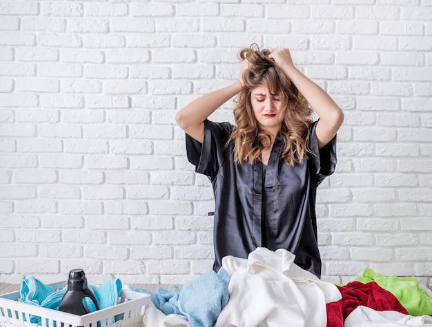 Zmęczona młoda kobieta robi pralni w domu