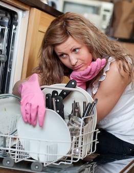 Zmęczona młoda kobieta segreguje zmywarka do naczyń