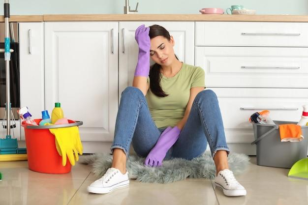 Zmęczona młoda kobieta siedzi na podłodze po sprzątaniu kuchni