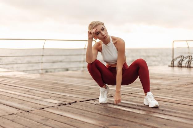 Zmęczona młoda kobieta sport o wschodzie słońca na plaży