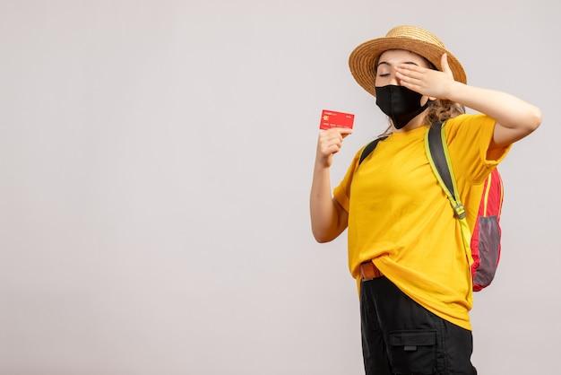 Zmęczona młoda kobieta z czarną maską trzymająca kartę na białym