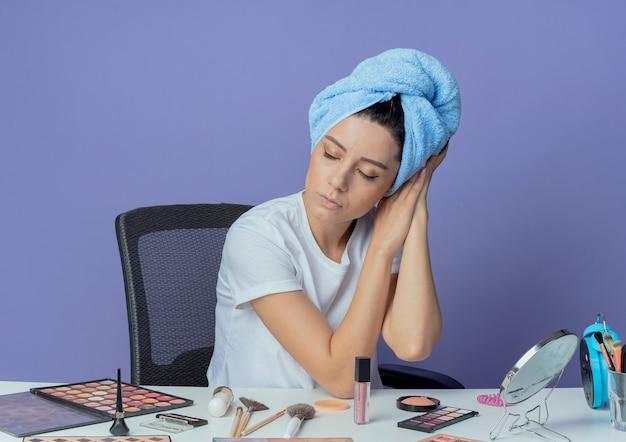 Zmęczona młoda ładna dziewczyna siedzi przy stole do makijażu z narzędziami do makijażu i ręcznikiem kąpielowym na głowie robi gest snu z zamkniętymi oczami