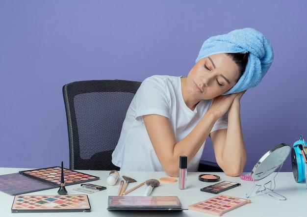 Zmęczona młoda ładna dziewczyna siedzi przy stole do makijażu z narzędziami do makijażu iz ręcznikiem na głowie robi gest snu z zamkniętymi oczami na białym tle na fioletowym tle