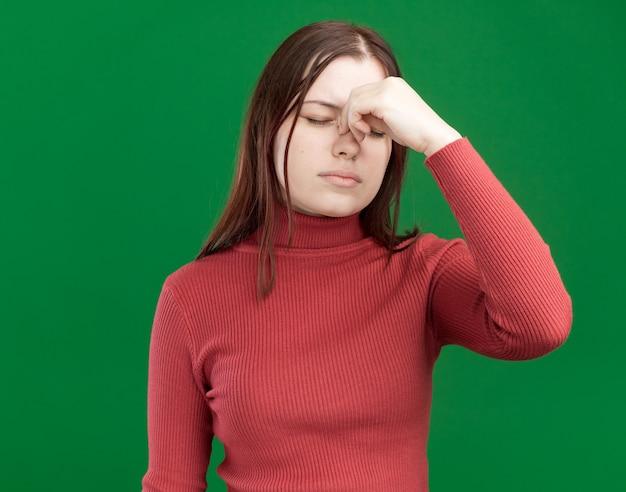 Zmęczona młoda ładna dziewczyna trzyma nos z zamkniętymi oczami