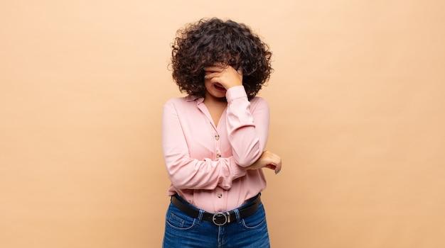 Zmęczona młoda ładna kobieta z kręconymi włosami