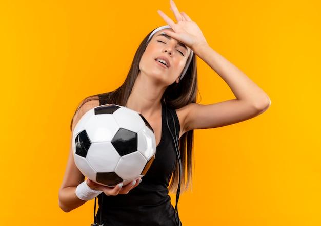 Zmęczona młoda ładna sportowa dziewczyna nosząca opaskę i opaskę na rękę trzymająca piłkę nożną kładąca dłoń na głowie z zamkniętymi oczami ze skakanką na szyi odizolowana na pomarańczowej przestrzeni