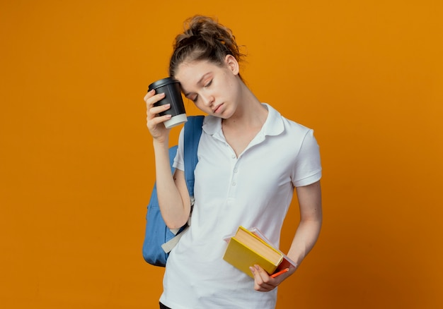 Zmęczona młoda ładna studentka nosząca tylną torbę z książkowym notesem i dotykającą głową plastikową filiżanką kawy z zamkniętymi oczami odizolowana na pomarańczowym tle z miejscem na kopię