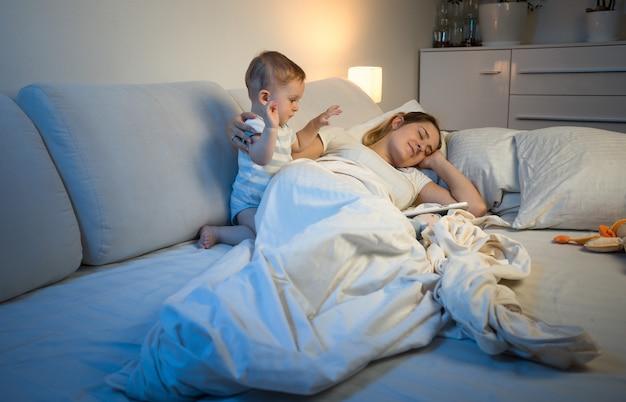 Zmęczona młoda matka próbuje zasnąć, podczas gdy jej dziecko budzi ją w nocy