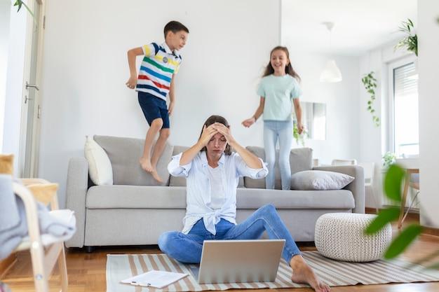 Zmęczona młoda matka siedzi na podłodze i pracuje z laptopem i dokumentami, podczas gdy małe dzieci skaczą na kanapie i bawią się i hałasują
