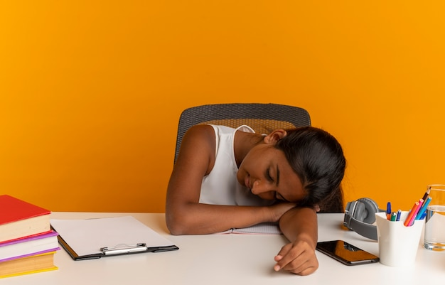 Zmęczona młoda uczennica siedzi przy biurku z narzędziami szkolnymi, kładąc głowę na biurku na białym tle na pomarańczowej ścianie