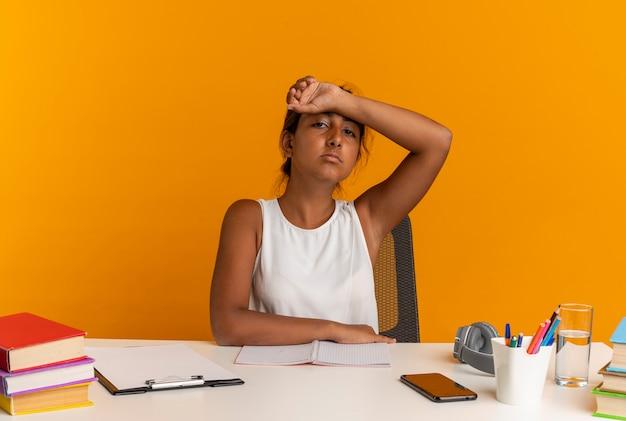 Zmęczona młoda uczennica siedzi przy biurku z narzędziami szkolnymi, kładąc nadgarstek na czole na białym tle na pomarańczowej ścianie