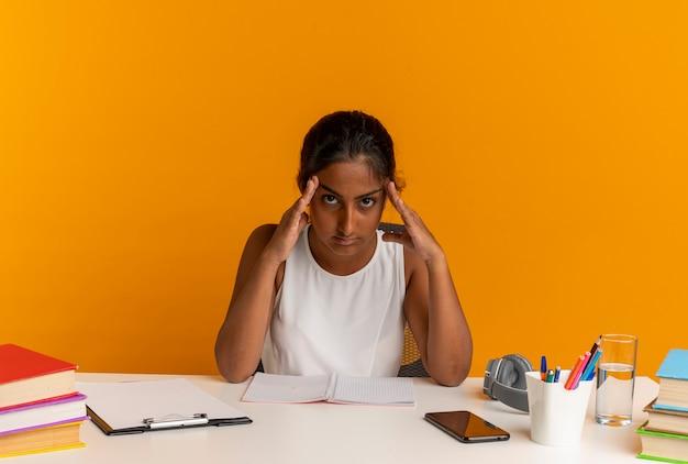Zmęczona młoda uczennica siedzi przy biurku z narzędziami szkolnymi, kładąc ręce na czole na białym tle na pomarańczowej ścianie