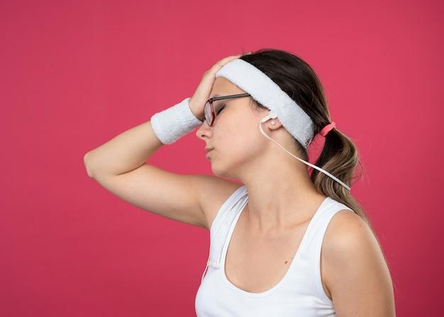 Zmęczona młoda wysportowana dziewczyna w okularach optycznych na słuchawkach w opasce i opaskach na nadgarstku kładzie rękę na czole